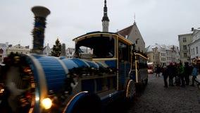 Jul marknadsför i Tallinn som åker skridskor barn på ett litet drev arkivfilmer