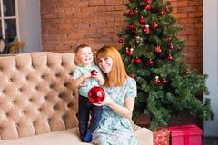 Jul x-mas, vinter, familj, folk, lyckabegrepp - den lyckliga modern med förtjusande behandla som ett barn pojken royaltyfri fotografi