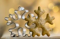 Jul metallisk och pepparkakasnöflingaskärare i magiska julljus på bakgrund Royaltyfri Bild