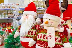 Jul mjuk leksak, snögubbe och Santa Claus Santa Claus med en vän i shoppar vindrutan royaltyfria bilder