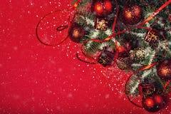 Jul och det nya året semestrar sammansättning på röd bakgrund med fallande snö- och kopieringsutrymme för din text royaltyfria foton