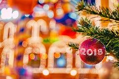 Jul och garneringbakgrund för nytt år Röd jul klumpa ihop sig på granfilial med text 2018 Royaltyfri Fotografi