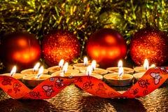 Jul och sammansättning för ` s för nytt år av röda bollar för julgranar och guld- glitter, i ljuset av stearinljus på en mörk bac arkivbilder