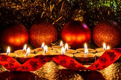 Jul och sammansättning för ` s för nytt år av röda bollar för julgranar och guld- glitter, i ljuset av stearinljus på en mörk bac arkivfoto
