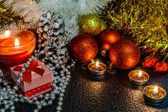 Jul och sammansättning för ` s för nytt år av röda bollar för julgranar och guld- glitter, i ljuset av stearinljus på en mörk bac royaltyfria foton