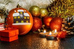 Jul och sammansättning för ` s för nytt år av röda bollar för julgranar och guld- glitter, i ljuset av stearinljus på en mörk bac arkivbild
