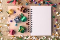 Jul och träbakgrundsbaner för nytt år med den tomma anteckningsboken, gåvaasken, tusenskönablomman, godisbollen och garnering på  royaltyfri bild