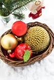 Julсomposition med julgarneringar i korg och Royaltyfria Foton