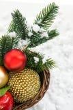 Julсomposition med julgarneringar i korg och Royaltyfri Fotografi