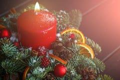 Jul röd stearinljus och prydnader över mörk bakgrund med ljus och copyspace Arkivbilder