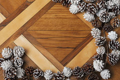Jul sörjer kottar på bakgrund av parketten Royaltyfri Bild