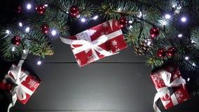Jul sammansättning och xmas-träd med suddiga blinkaljus, gåvor med det fina vita bandet på den svarta trätabellen stock video