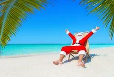 Jul Santa Claus på sunlounger som är lycklig med, gömma i handflatan ferier för sandig strand royaltyfri bild