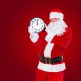 Jul Santa Claus som pekar på klockan som visar fem minuter till midnatt Arkivfoto