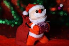 Jul santa med gåvapåsen och den purpurfärgade gilfasken royaltyfri bild