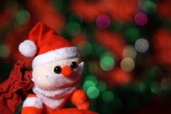 Jul santa som klättrar med gåvapåsen på röd och grön bakgrund arkivbilder