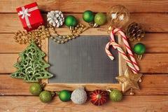 Jul semestrar bakgrund med den tomma svart tavlan på trätabellen och julpynt royaltyfria foton