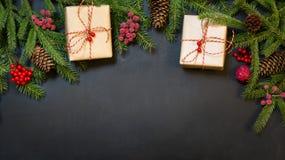 Jul semestrar bakgrund - träd, gåvor, järnekbär och garnering på en svart chackboard Feriekort med kopieringsutrymme Beskåda Royaltyfri Fotografi