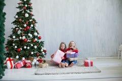 Jul semestrar flicka två med julgranen för det nya året för gåvor på gråa gåvor för en bakgrund royaltyfria foton