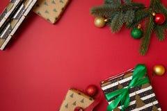 Jul semestrar sammansättning på röd bakgrund med kopieringsutrymme för din text Filialer för Xmas-trädgran med bollen i hörnet, g royaltyfria foton