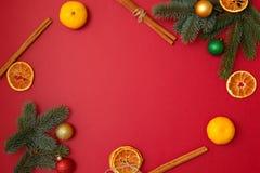 Jul semestrar sammansättning på röd bakgrund med kopieringsutrymme för din text Xmas-trädfilialer i hörnen, torkade apelsiner, royaltyfri bild