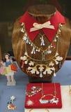 Jul shoppar fönsterskärm av Les Nereides Paris Halsband för krage för kvinna` s med themed berlock för jul Royaltyfria Bilder