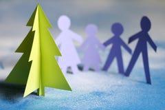 Jul skyler över brister trädet och familjen Arkivfoton