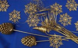 Jul smyckar blå bakgrund för guld- snöflingor arkivfoto