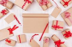 Jul som annonserar bakgrund med den tomma hantverknotepaden, gåvor med den röda blyertspennan, pilbågar och bandet på det vita tr royaltyfria bilder