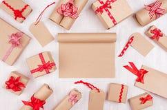 Jul som annonserar bakgrund med den tomma hantverknotepaden och olika gåvor med röda pilbågar och bandet på det vita träbrädet royaltyfria foton
