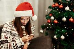 Jul som annonserar begrepp stilfull looki för kvinnainnehavtelefon arkivfoto