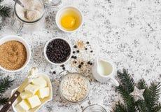 Jul som bakar bakgrund Pudra, sockra, breda smör på, rullande havre, ägg, chokladchiper på en ljus bakgrund arkivbild