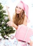 jul som dekorerar den flickahjälpredasanta treen Royaltyfria Bilder