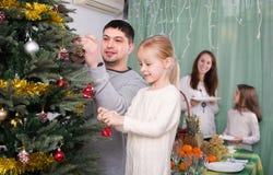 jul som dekorerar den home treen för familj Arkivbild