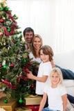 jul som dekorerar den lyckliga treen för familj Arkivbild
