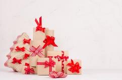 Jul som förbereder sig - askar för gåvainpackning av kraft med röda band och pilbågar och julträdet på den vita trätabellen fotografering för bildbyråer
