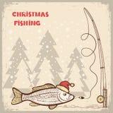 Jul som fiskar kortet med fisken i röd jultomtenhatt. Royaltyfri Foto