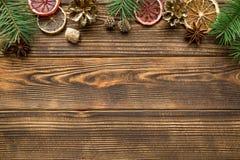 Jul som hälsar bakgrund Driend apelsiner som är guld- sörjer kottar, kryddor, som anis och kanel, granträdfilialer på brunt royaltyfri foto