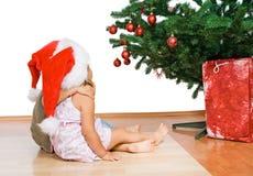 jul som kramar ungar som ser treen Royaltyfri Fotografi