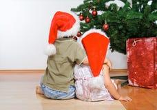 jul som kramar ungar som ser treen royaltyfria bilder