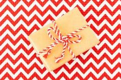 Jul som lägenhet-är lekmanna- av den hand tillverkade gåvaasken av kraft inpackningspapper på rött med den vita textilbordduken arkivbilder