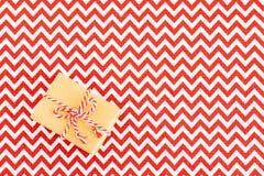 Jul som lägenhet-är lekmanna- av den hand tillverkade gåvaasken av kraft inpackningspapper på rött med den vita textilbordduken royaltyfria foton