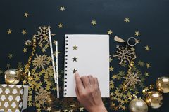 Jul som planerar upp begreppsåtlöje Anteckningsbok för kvinnahandorganisation på det svarta bakgrundswashibandet, guld- stjärnako royaltyfri fotografi
