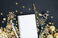 Jul som planerar upp begreppsåtlöje Anteckningsbok på svart bakgrund med washibandet, guld- stjärnor konfettier, gåvan, slingrand fotografering för bildbyråer