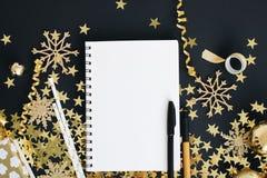 Jul som planerar upp begreppsåtlöje Anteckningsbok på svart bakgrund med washibandet, guld- stjärnor konfettier, gåvan, slingrand arkivbild