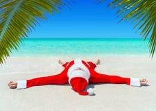 Jul som Santa Claus solbadar på det tropiska havet, gömma i handflatan den sandiga stranden Arkivbilder