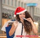 Jul som shoppar, flicka som rymmer färgrika shoppingpåsar som bär den santa hatten Royaltyfria Bilder