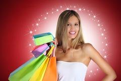 Jul som shoppar kvinnan med färgrika påsar på röd bakgrund Royaltyfri Bild