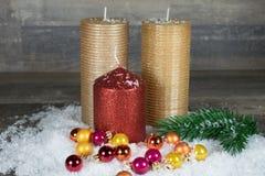 Jul stearinljus i snön med färgrika bollar Arkivfoton