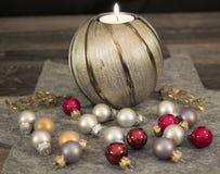 Jul stearinljus med julbollar Arkivfoto